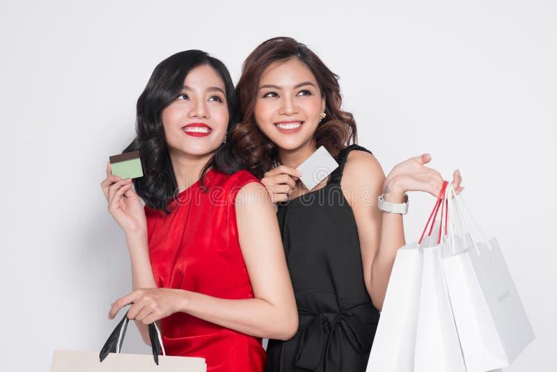 Twee gelukkige aantrekkelijke jonge vrouwen met de holding van de creaditkaart shopp stock foto