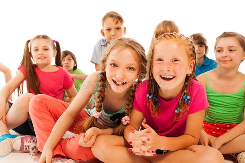 Twee gelukkige babbelende meisjes zitten in groep vrienden royalty-vrije stock foto