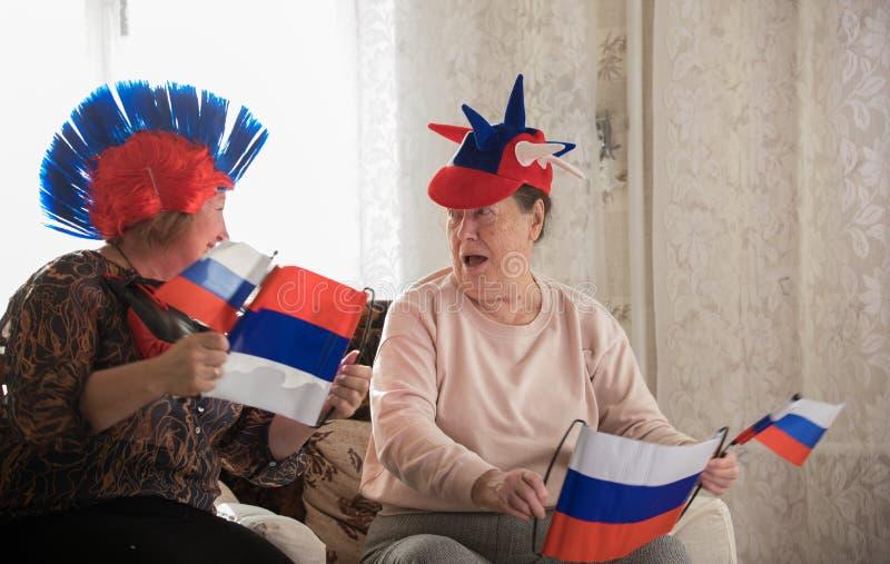 Twee gelukkige bejaarden die op TV in Russische toebehoren letten royalty-vrije stock afbeelding