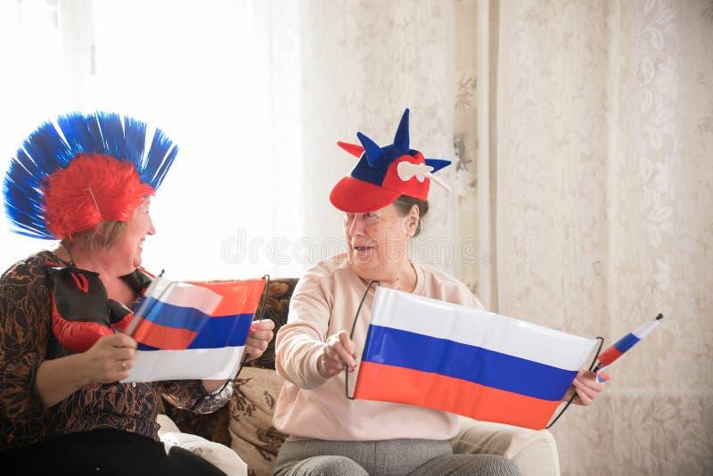 Twee gelukkige bejaarden in Russische toebehoren met vlaggen stock fotografie