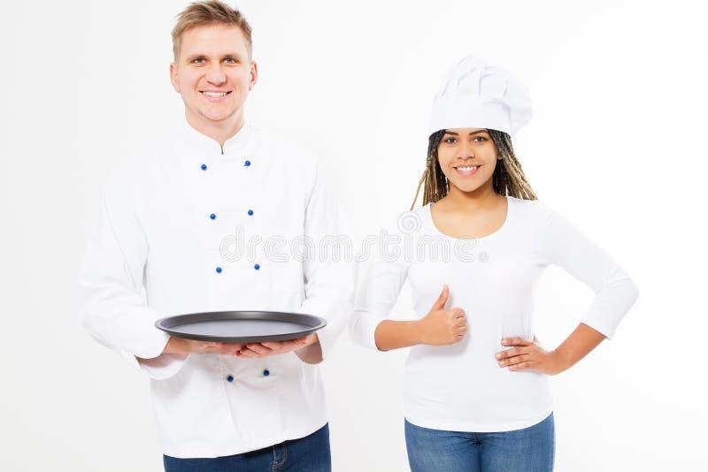 Twee gelukkige glimlachchef-koks die een leeg dienblad houden en tonen als teken dat op wit wordt geïsoleerd Wit en afro Amerikaa royalty-vrije stock afbeeldingen