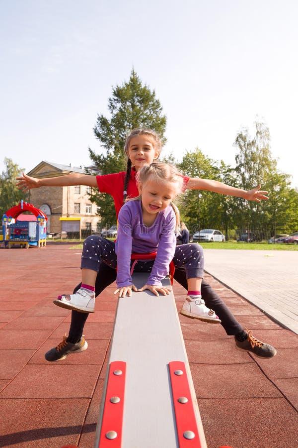 Twee gelukkige glimlachende Kaukasische meisjes die pret op speelplaats hebben, die uitgestrekte geschommelwapens berijden, verti royalty-vrije stock foto's
