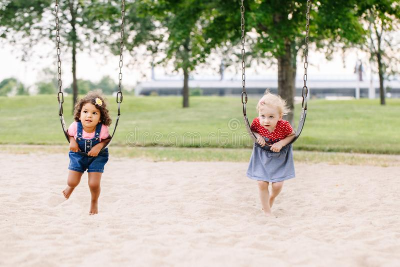 Twee gelukkige glimlachende kleine vrienden die van peutersmeisjes op schommeling bij speelplaats buiten slingeren royalty-vrije stock foto