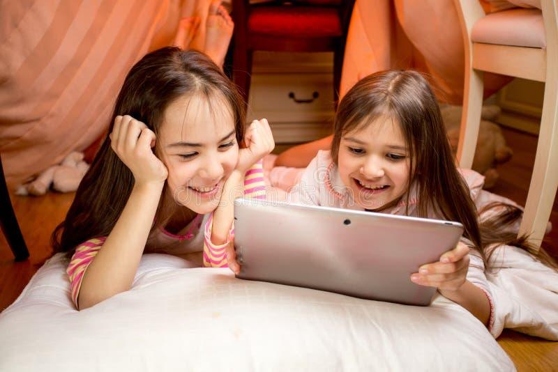 Twee gelukkige glimlachende meisjes die op vloer liggen en digitale tablet gebruiken stock foto's