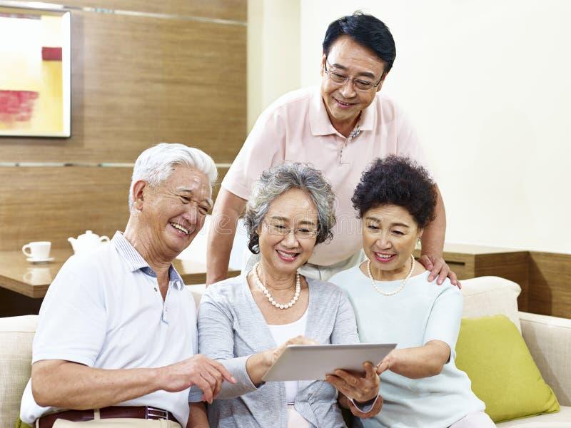 Twee gelukkige hogere Aziatische paren die tabletcomputer thuis met behulp van stock fotografie