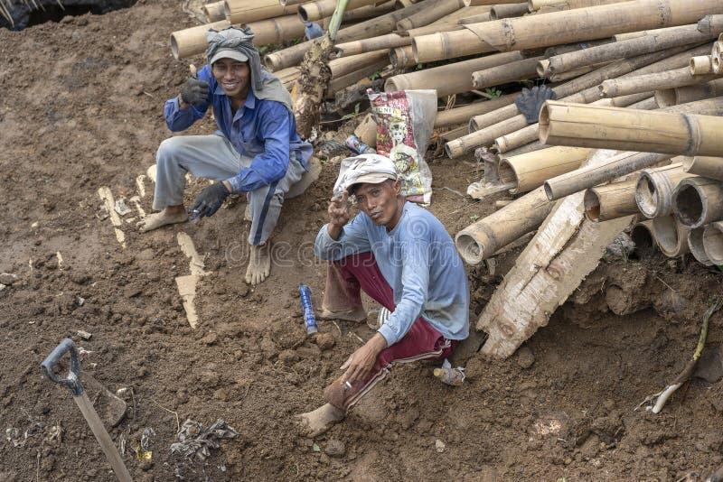 Twee gelukkige Indonesische arbeiders rusten na grondwerken in Ubud, eiland Bali, Indonesië stock foto's