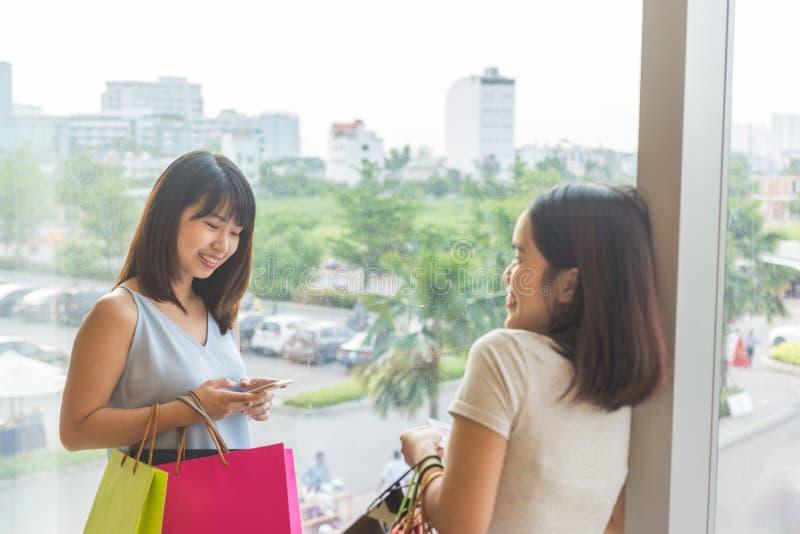 Twee gelukkige jonge dames die aardige tijd bij het winkelen hebben stock fotografie