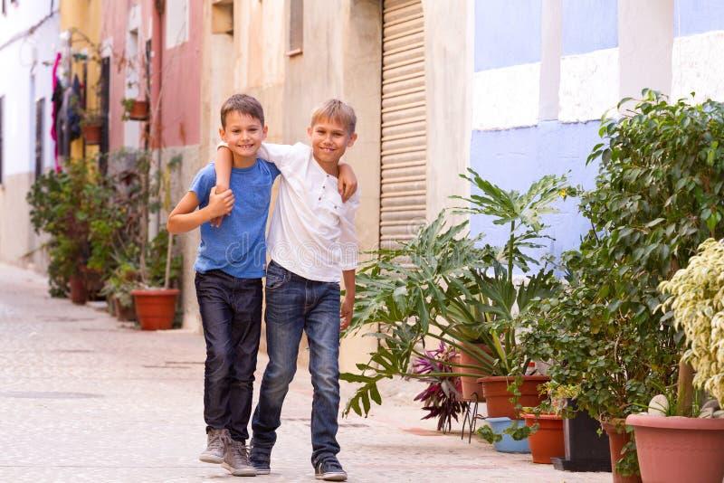 Twee gelukkige jonge geitjes in openlucht in de straat Europese stad op de zomerdag stock foto