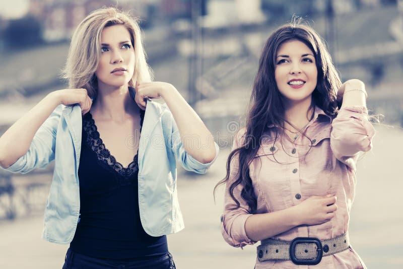 Twee gelukkige jonge maniervrouwen die op stadsstraat lopen royalty-vrije stock fotografie