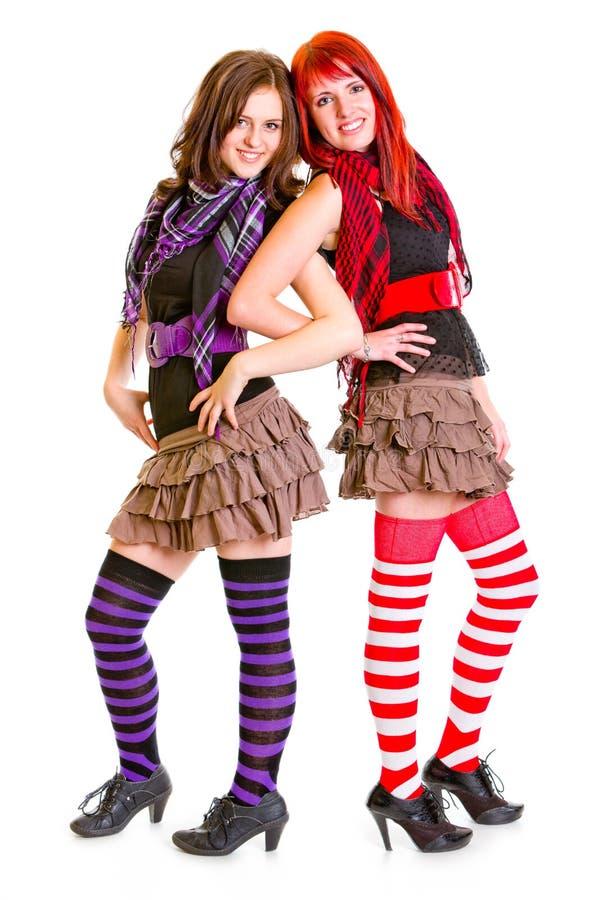 Twee gelukkige jonge meisjes die zich rijtjes bevinden royalty-vrije stock afbeeldingen