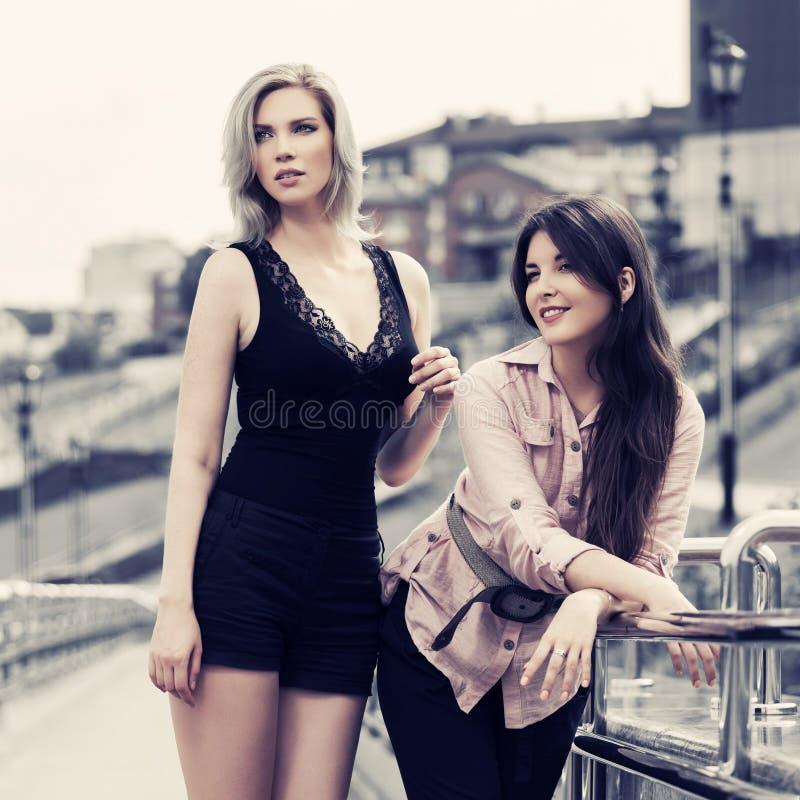 Twee gelukkige jonge modevrouwen op straat stock foto