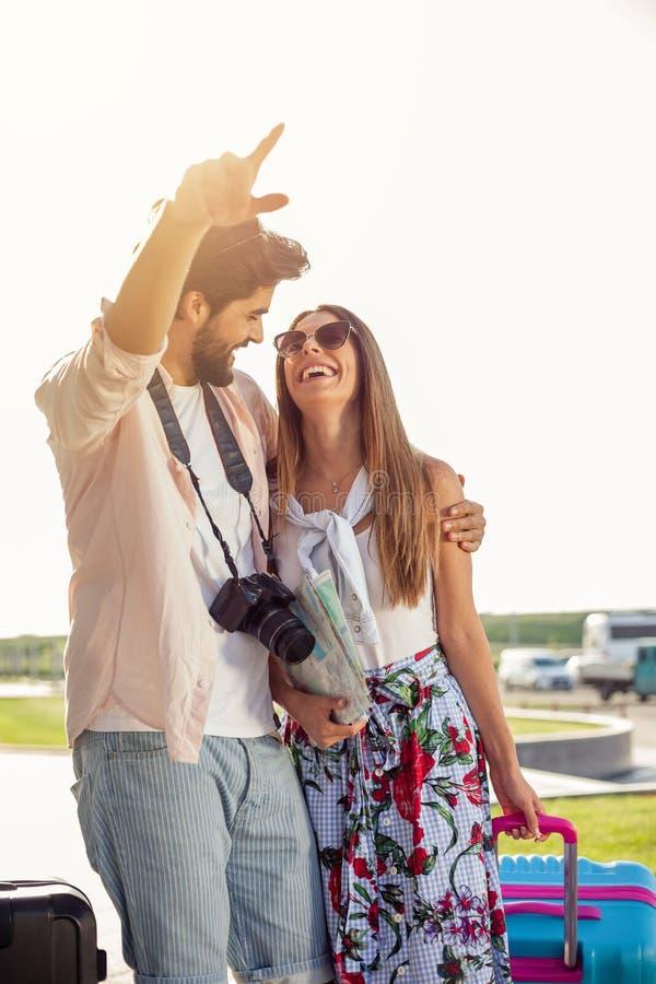Twee gelukkige jonge toeristen die nieuwe stad onderzoeken, die onderaan de straat loopt die in HU wordt omhelst royalty-vrije stock fotografie