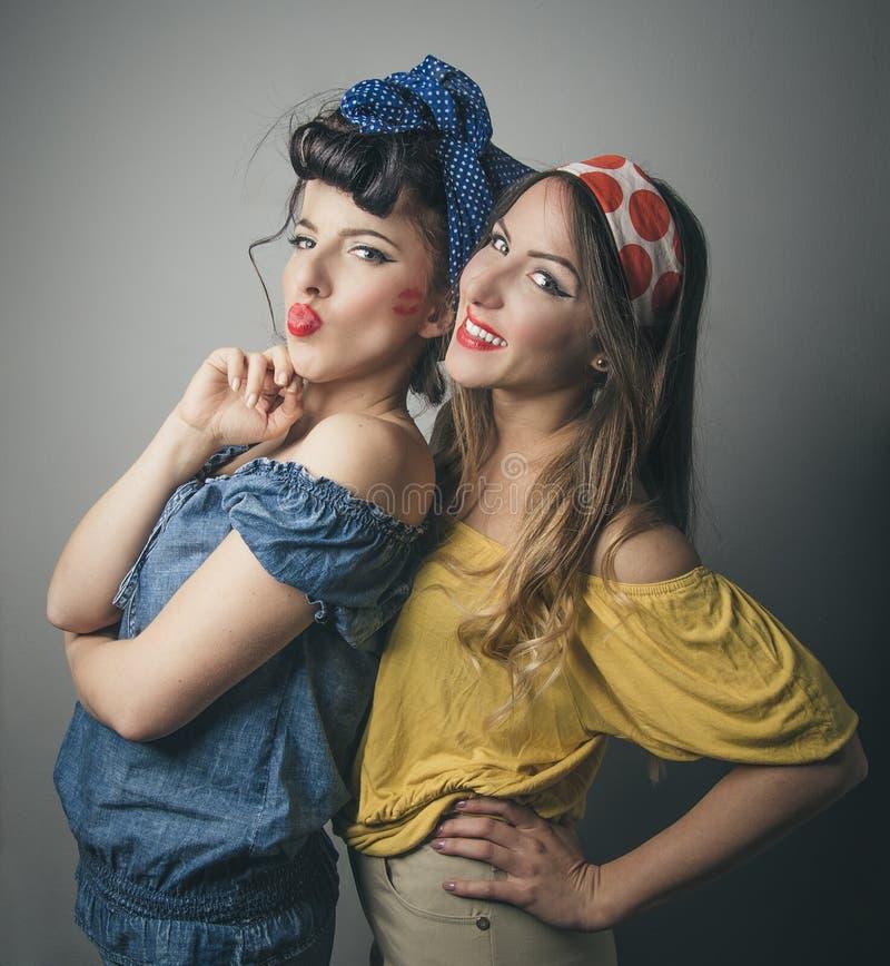 Twee gelukkige jonge vrouwelijke vrienden in retro kleding stock foto