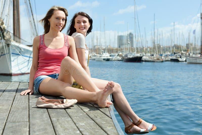 Twee gelukkige jonge vrouwen die op de ligplaats zitten royalty-vrije stock foto