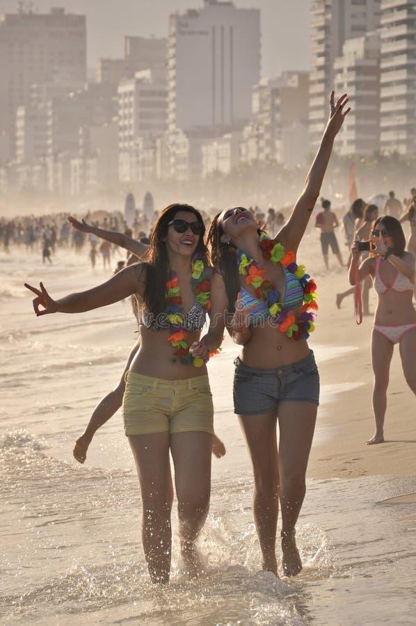 Twee gelukkige jonge vrouwen genieten van Carnaval in Ipanema-strand stock afbeelding