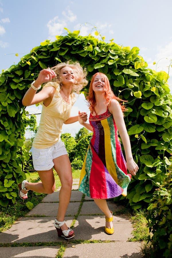 Twee gelukkige jonge vrouwen runing in een park stock afbeeldingen