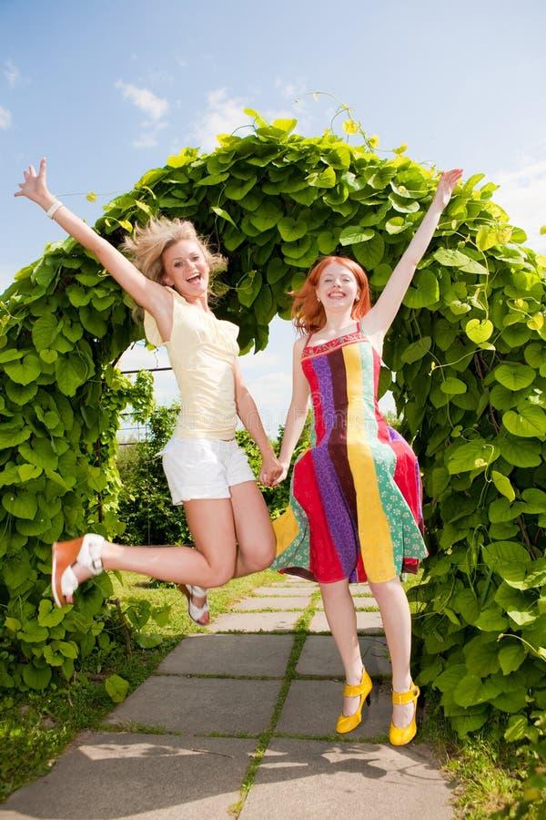 Twee gelukkige jonge vrouwen runing in een park stock foto