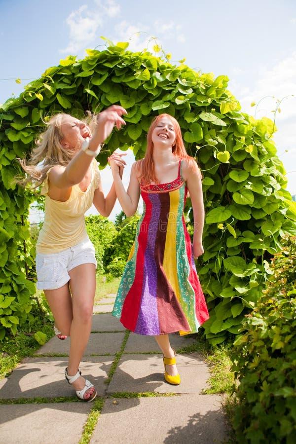 Twee gelukkige jonge vrouwen runing in park stock afbeeldingen