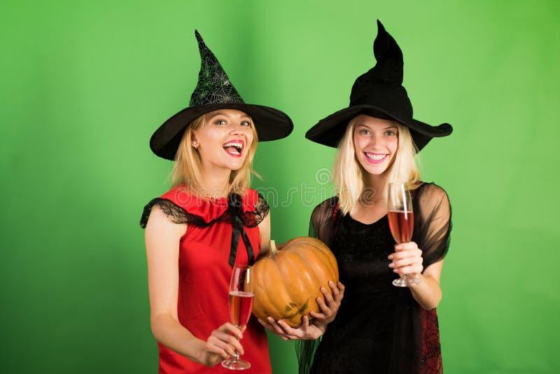 Twee gelukkige jonge vrouwen in zwart en rood kleedt zich, kostuumsheksen Halloween op partij over groene achtergrond feestelijk stock afbeeldingen