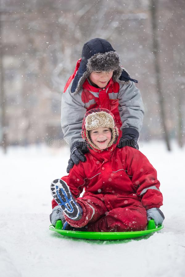Twee gelukkige jongens die bij de dia op sneeuwpark berijden stock fotografie