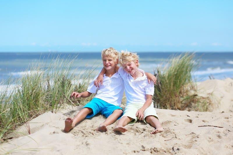 Twee gelukkige jongens die in duinen bij het strand spelen stock foto