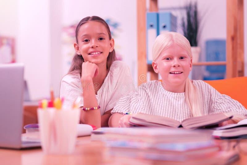 Twee gelukkige kinderen die bij het bureau zitten royalty-vrije stock foto's