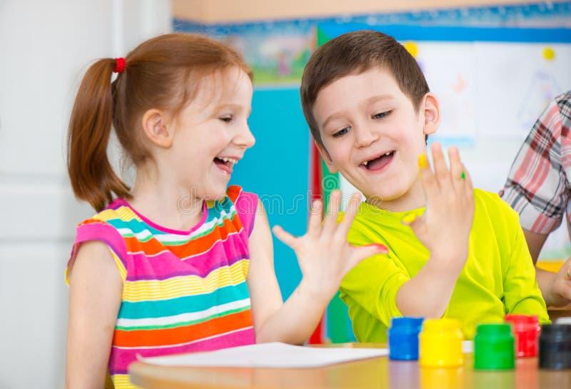 Twee gelukkige kinderen die met kleurrijke verven trekken stock foto