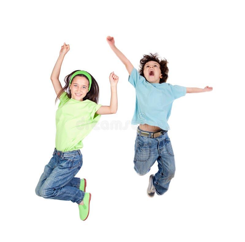 Twee gelukkige kinderen die meteen springen stock fotografie