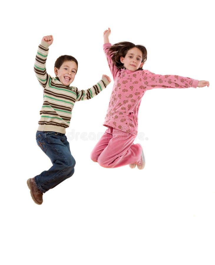 Twee gelukkige kinderen die meteen springen stock afbeeldingen