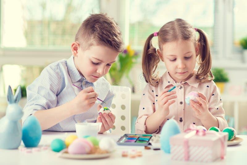 Twee gelukkige kinderen die pret hebben tijdens het schilderen eieren voor Pasen binnen royalty-vrije stock afbeeldingen
