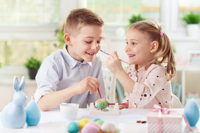 Twee gelukkige kinderen die pret hebben tijdens het schilderen eieren voor Pasen binnen royalty-vrije stock afbeelding