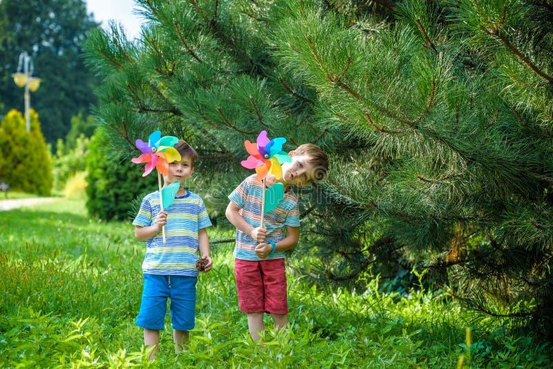 Twee gelukkige kinderen die in tuin met windmolenvuurrad spelen De aanbiddelijke sibling broers zijn beste vrienden De leuke de g stock foto's