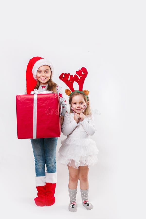 Twee gelukkige kleine het glimlachen jonge geitjes in van Kerstmanhoed en herten hoornen met de de grote doos en snoepjes van de  royalty-vrije stock foto's