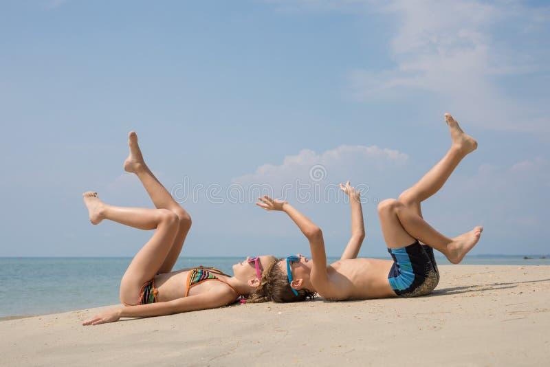 Twee gelukkige kleine kinderen die op het strand in de dagtijd spelen royalty-vrije stock afbeelding