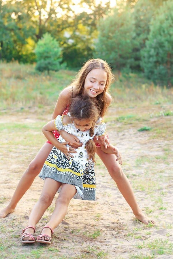 Twee gelukkige kleine meid die omarmt en speelt op zomerdag royalty-vrije stock foto's