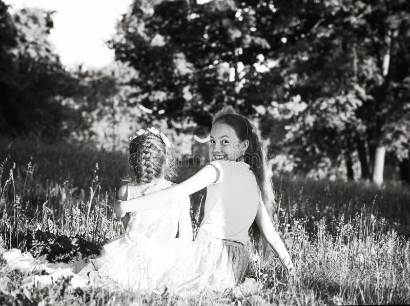 Twee gelukkige kleine meisjes die lachen en knuffelen in het zomerpark Happy chidhood-concept Zwart-witte foto stock foto's