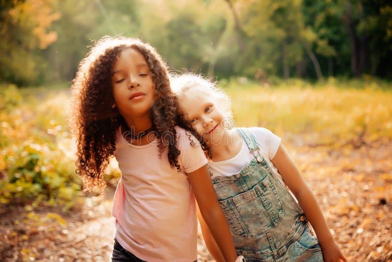 Twee gelukkige meisjes als vriendenomhelzing elkaar op vrolijke manier Kleine meisjes in park stock fotografie