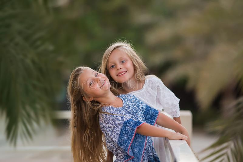 Twee gelukkige meisjes als vriendenomhelzing elkaar op vrolijke manier Kleine meisjes in park Kinderenvriendschap die samen gliml stock foto