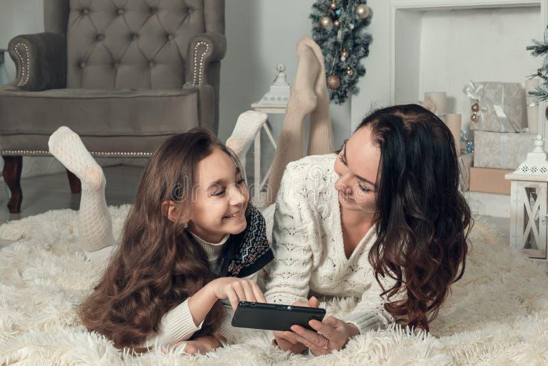 Twee gelukkige meisjes, de moeder en de dochter liggen op een vloer in Nieuwjaar royalty-vrije stock fotografie