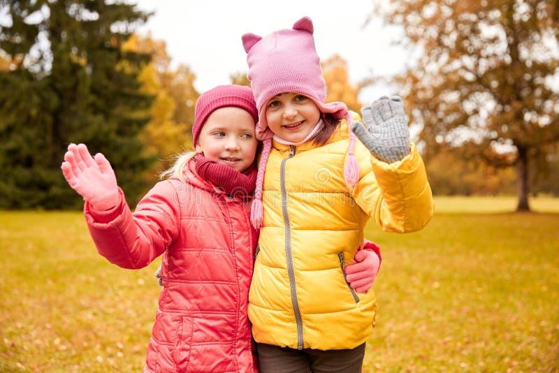 Twee gelukkige meisjes die dienen de herfstpark in golven stock fotografie