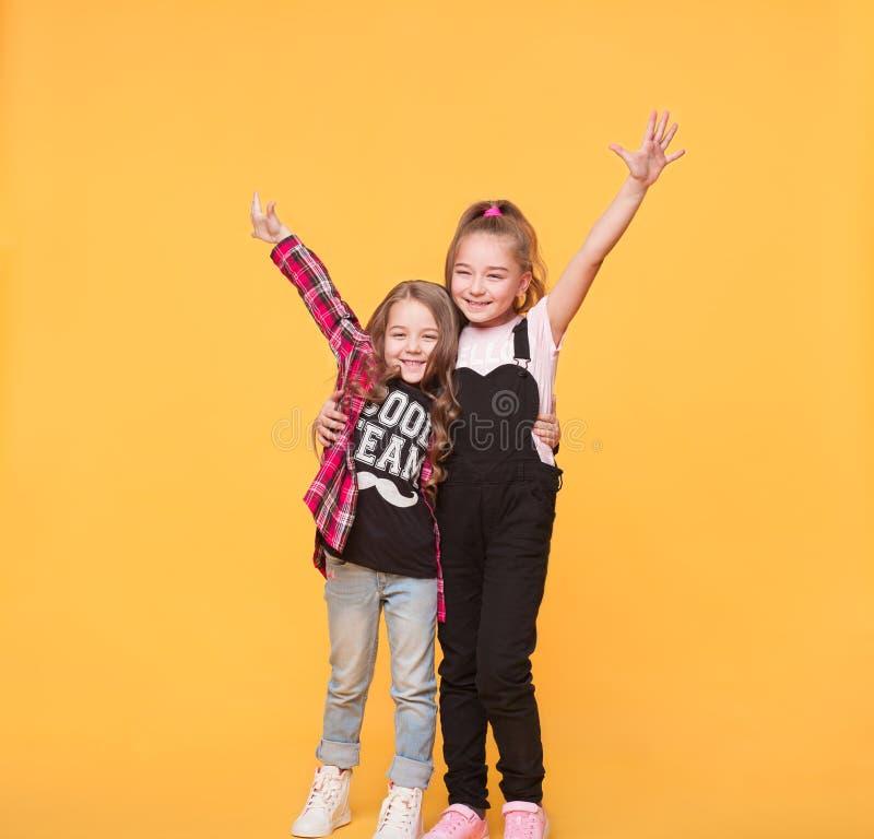 Twee gelukkige meisjes die elkaar omhelzen stock fotografie