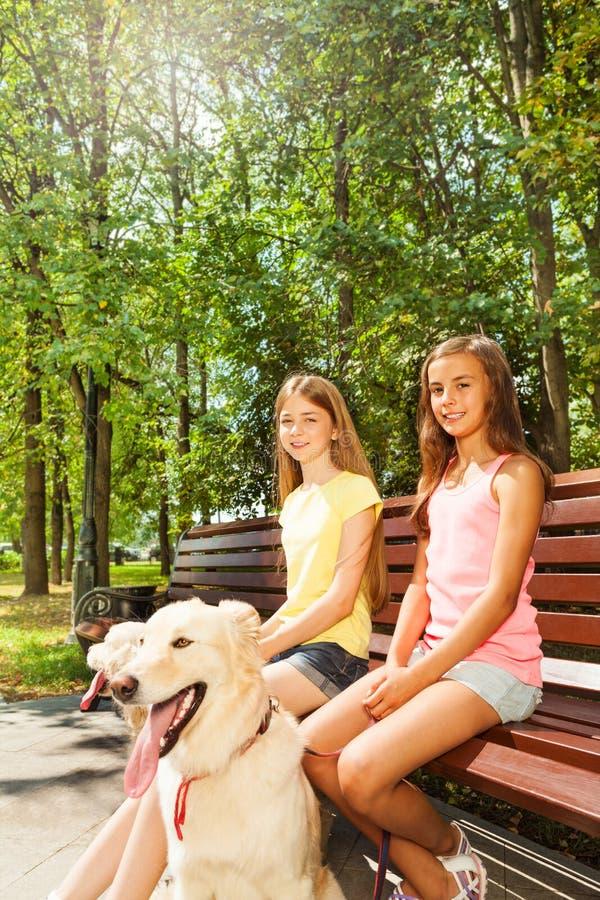 Twee gelukkige meisjes die op de bank in park zitten stock foto's