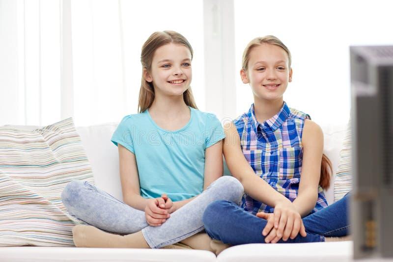 Twee gelukkige meisjes die op TV thuis letten stock foto