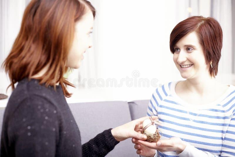 Twee gelukkige meisjes die paasei geven stock foto