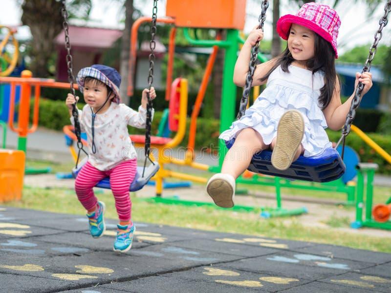 Twee Gelukkige meisjes die schommeling spelen bij de speelplaats Gelukkig, F stock fotografie