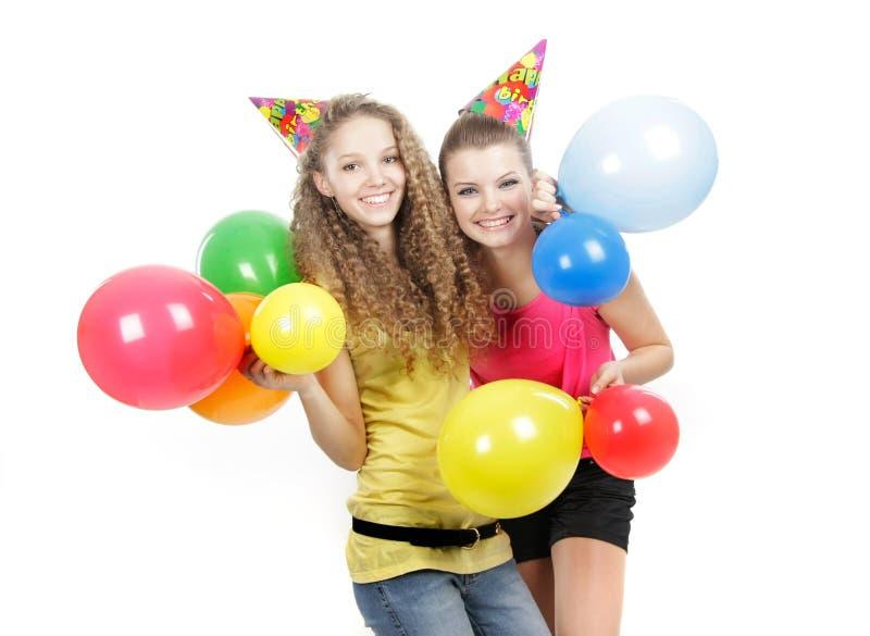 Twee gelukkige meisjes met kleurrijke ballons stock afbeeldingen