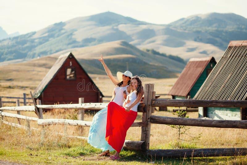 Twee gelukkige meisjes ontspannen bij platteland royalty-vrije stock afbeeldingen