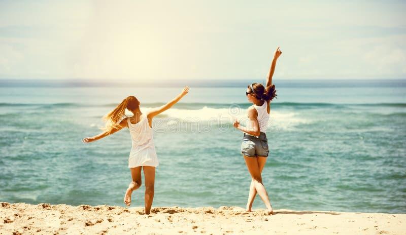 Twee gelukkige meisjes overzeese strandpret royalty-vrije stock foto
