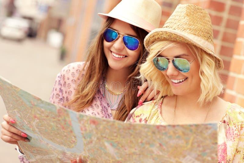 Twee gelukkige meisjesvrienden die de stad bezienswaardigheden bezoeken royalty-vrije stock fotografie