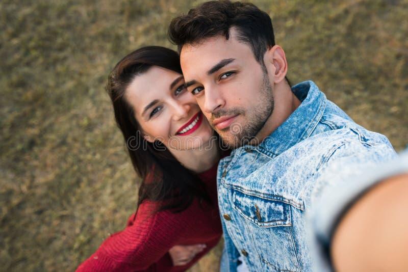 Twee gelukkige minnaarsmensen die dateren zij, omhelzend elkaar, die selfie met liefde die openlucht ogen volledig van geluk hebb stock afbeelding